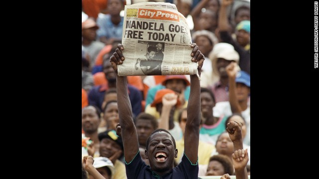 A jubilant South African holds up a newspaper announcing Mandela's release from prison at an ANC rally in Soweto on February 11, 1990.