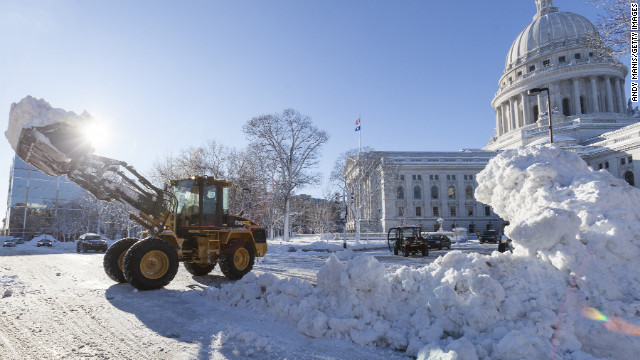 Crews remove pile up snow from around the Capitol Square in Madison, Wisconsin, on Friday, December 21. A winter storm system that walloped the Midwest continues to move east bringing snow and wind to Ohio, Pennsylvania and upstate New York.