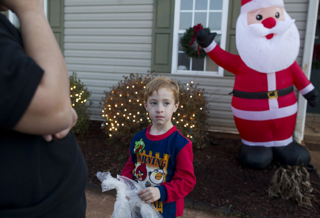 Standing with his mother, left, Chase Evans, 5, plugs in an inflatable Santa Claus at their home.