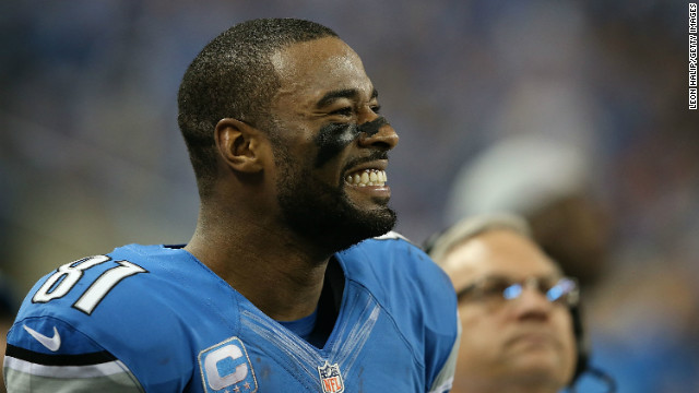 Calvin Johnson of the Detroit Lions smiles after breaking the NFL single season yardage record formally held by Jerry Rice .