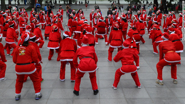 Members of a local yoga club perform at a public park wearing Santa Claus costumes in Hanoi, Vietnam, on December 23.