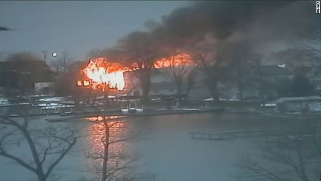 Flames tear through a house in Webster, New York, where shots were fired at firefighters Monday.