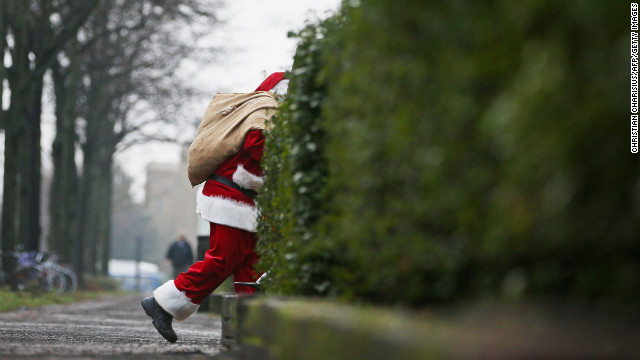 A man decked out as Santa Claus slips through the back streets of Hamburg, Germany, on Monday, December 24. Related photos: Magnum Santas
