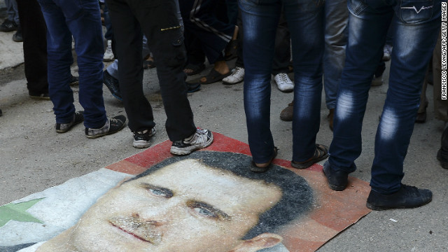 Syrian protesters step on President al-Assad's portrait during an anti-regime demonstration in Aleppo on November 16, 2012. 