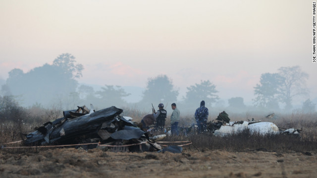 Security officers stand guard at the crash site of a plane near Myanmar's Heho Airport on Wednesday, December 26. The plane crashed near the airport Tuesday, December 25, leaving two people dead and injuring 11others.