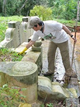 Millie Phuah clears leaves from the tomb of her great-grandparents in Bukit Brown cemetery.
