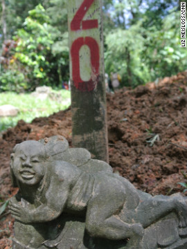 A Chinese stone carving is seen on a grave marked for exhumation in Bukit Brown cemetery. 