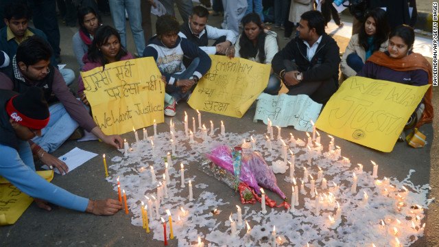Indian protesters sit by lit candles and hold placards in New Delhi on December 30 during a protest against the gang rape.
