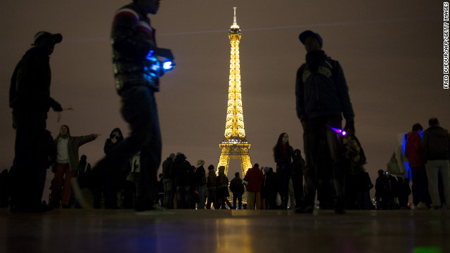 People gather as they celebrate the arrival of 2013 on Trocadero Square beside the Eiffel Tower in Paris.