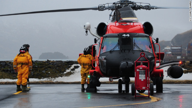 Coast Guard crews load onto a helicopter.