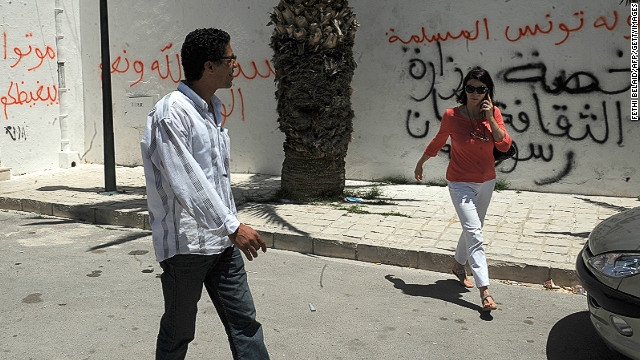 Tunis residents walk past graffiti left by rioters on a building housing a controversial art exhibition in the Tunisian capital in June 2012. The graffiti messages read: &quot;God is great,,&quot; &quot;Non-believers have no place in Tunisia&quot; and &quot;You are enemies of God.&quot;