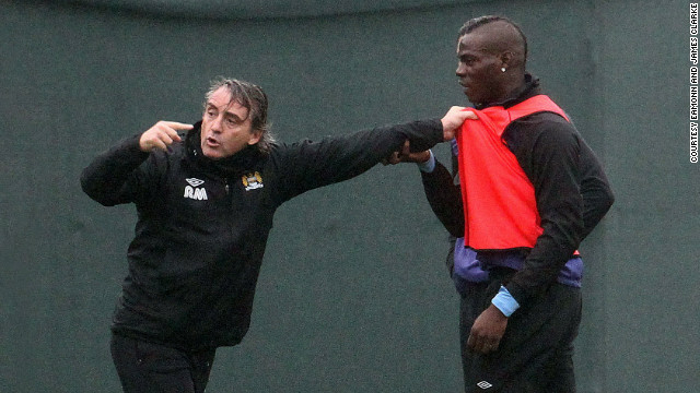Manchester City manager Roberto Mancini was photographed grappling with his firebrand striker Mario Balotelli during a training run on Thursday, prompting coaching staff to intervene to separate the pair. Mancini later downplayed the tussle, sparked by Balotelli's hostile tackle on a fellow player, as &quot;nothing unusual.&quot;