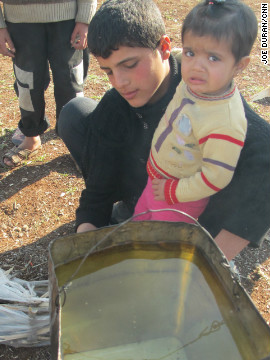 Muhammad Yousef, 14, holds his 1-year-old sister, Rama, as he heats water for his mother to wash clothes.