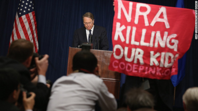 An anti-gun activist holds up a banner as NRA leader Wayne LaPierre talks about the Newtown, Connecticut, school slaughter.