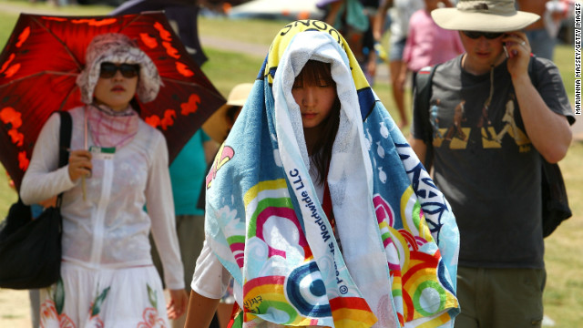 Tourists cover themselves with towels to protect themselves from the sun on one of the hottest days on record.