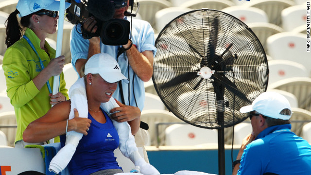 Officials decided not to suspend play despite scorching heat. Here, world No. 10 Caroline Wozniacki makes use of a fan and an ice towel during a break in her match.