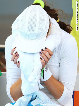 Qualifier Galina Voskoboeva buries her face in an ice towel during a break in her defeat to Germany's Angelique Kerber. The Russian had to take a medical time out after struggling with the heat.