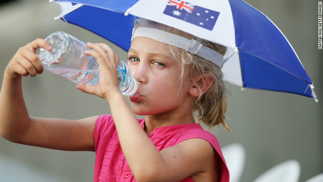 A young fan takes on water under the shade of their umbrella at Sydney Olympic Park.