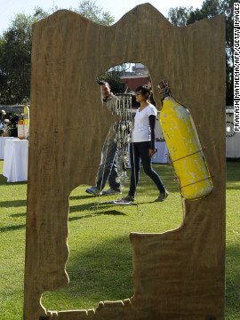 A visitor walks past an artwork made with an oxygen cylinder and plywood. 