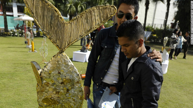 "Visitors look at art made from trash collected on Mount Everest, commissioned for the ""Mt. Everest 8848 Art Project"" in Kathmandu on November 19, 2012."