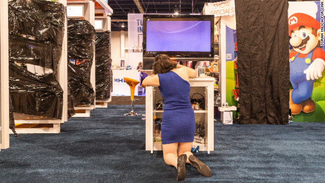 A woman prepares to open the Innex Inc. booth, which is showing its Rock Candy game controllers at the second day of the Consumers Electronic Show on Wednesday.
