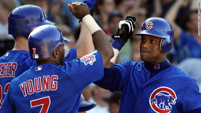 Chicago Cubs slugger Sammy Sosa, right, is congratulated at the plate by his teammates after scoring in a game against the San Francisco Giants on August 10, 2001, at Wrigley Field in Chicago.