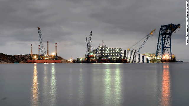 Cranes and floating decks surrounding the ship light up the dusk on Wednesday.