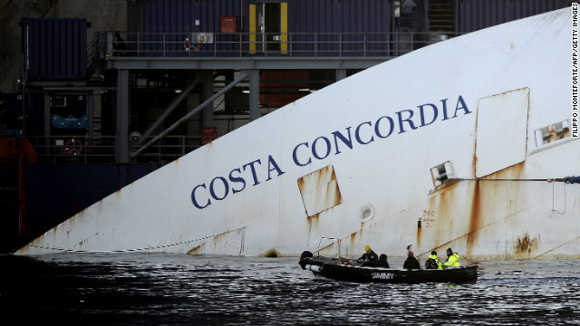 Workers in a small boat pass by the Costa Concordia on Monday, January 7. &lt;a href='http://www.cnn.com/2012/01/14/europe/gallery/italy-ship/index.html'&gt;See photos from the shipwreck in 2012.&lt;/a&gt;
