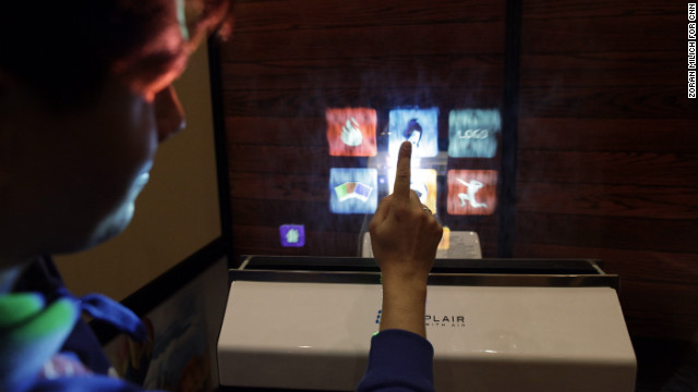An attendee uses a water-based touch screen computer monitor created by Displair on January 10.