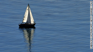 A boat sails across the peaceful waters of Lake Geneva.