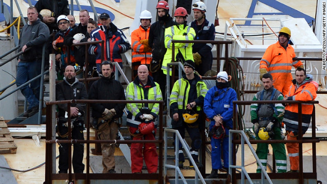 Workers stand on the wrecked Costa Concordia cruise ship off the Italian island of Giglio on Sunday, January 13, during commemorations marking the first anniversary of the cruise liner disaster. Survivors, grieving relatives and locals on the island of Giglio gathered to remember the 32 people who were lost.