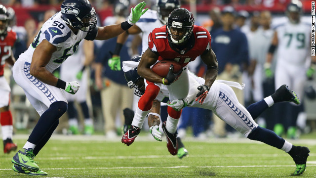 Julio Jones of the Atlanta Falcons is tackled by No. 50 K.J. Wright and No. 25 Richard Sherman of the Seahawks in the third quarter on Sunday.