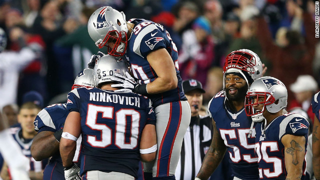 Rob Ninkovich of the New England Patriots, No. 50, celebrates with Niko Koutouvides after making an interception against the Houston Texans during the 2013 AFC divisional playoff game at Gillette Stadium in Foxboro, Massachusetts, on Sunday, January 13. The Patriots defeated the Texans 41-28.