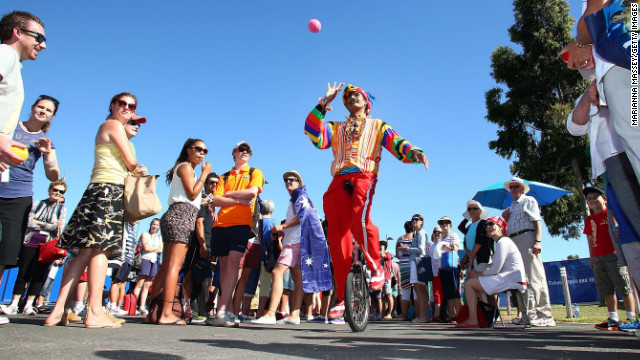 A juggler entertains the crowd as they wait to enter the grounds at Melbourne Park for Day 2 of the Australian Open.