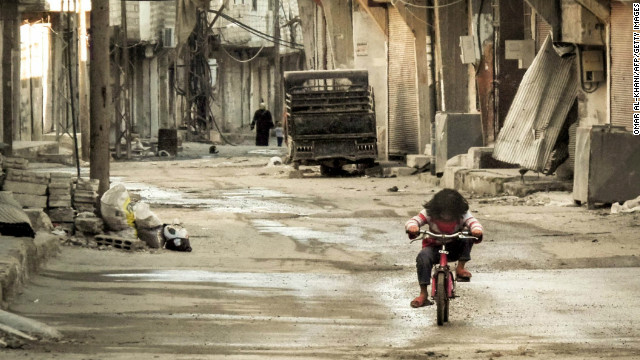 A Syrian girl rides her bicycle in an almost deserted street in Damascus, Syria on January 3, 2013.