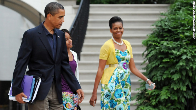 Obama has been known to wear dresses from mass retailer Talbots and accessorize them with signature pieces such as this sweater from Dear Cashmere and a belt by Sonia Rykiel, worn in July 2009, <a href='http://mrs-o.com/newdata/2009/7/5/bon-voyage.html' target='_blank'>according to style blog Mrs. O</a>.