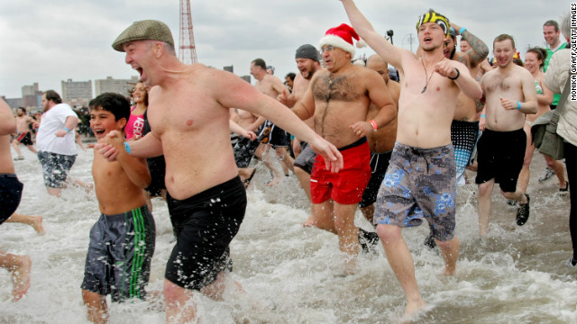 People run into the Atlantic Ocean as part of the Coney Island Polar Bear Club's New Year's Day swim in New York. 