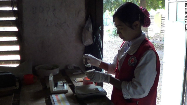 Red Cross volunteer Tin Tin Wae measures chlorine powder for drinking water that will be distributed to camps where displaced people are now living in Rakhine state.