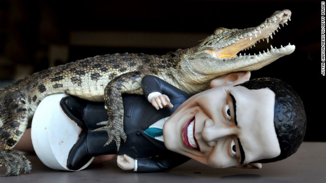 AUSTRALIA: &quot;Charlie,&quot; a baby saltwater Crocodile, grabs a figurine of Obama at Crocodylus Park on October 18, 2011, in Darwin, Northern Territory.