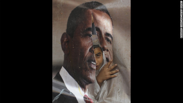 PAKISTAN: An activist of Awami Majlis-e-Amal looks through a torn poster of Obama during a protest against the reopening of the NATO supply route to Afghanistan in Quetta on July 13, 2012.