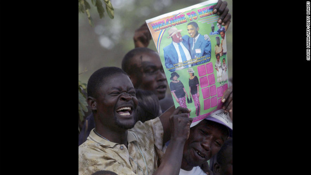 KENYA: A resident of Kisumu raises a poster bearing Obama's likeness after an HIV/AIDS test on August 26, 2006. Obama urged residents of the area to get tested for HIV and AIDS so they would know their status.