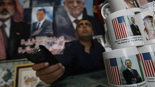 GAZA: A Palestinian shopkeeper sits near coffee mugs for sale with pictures of Obama and Hamas leader Ismail Haniya on November 2, 2008, in Gaza City. The mugs read &quot;Hey!!! Come and drink the Palestinian coffee with the flavor of the US Presidential Election.&quot;