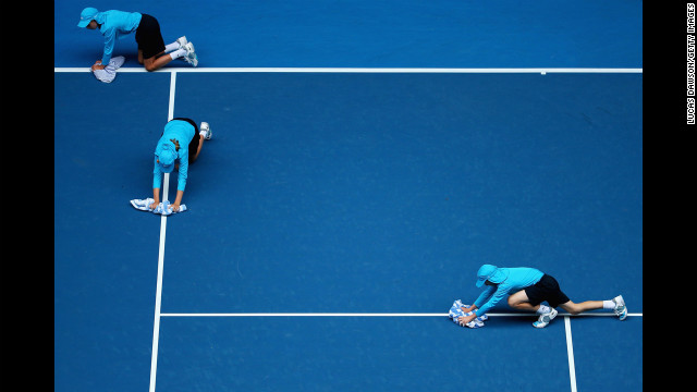 Ball kids dry the court during a rain delay on January 18.