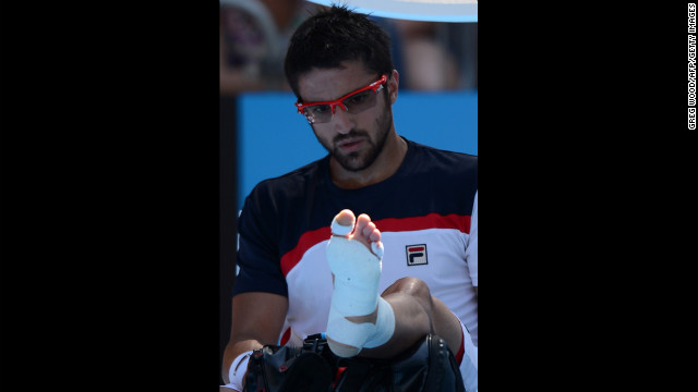 Serbia's Janko Tipsarevic looks at his wrapped foot during a break in his men's singles match against Spain's Nicolas Almagro on January 20. Almagro moved on to the next round after Tipsarevic pulled out of the match in the second set because of his injury.