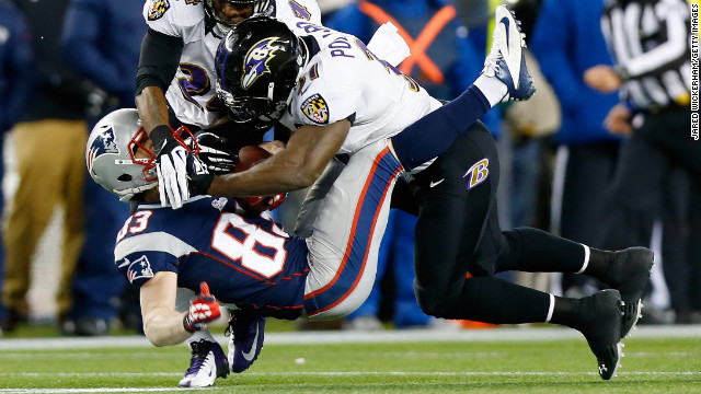 Wes Welker of the New England Patriots is tackled by Bernard Pollard and Corey Graham of the Baltimore Ravens after catching a pass.