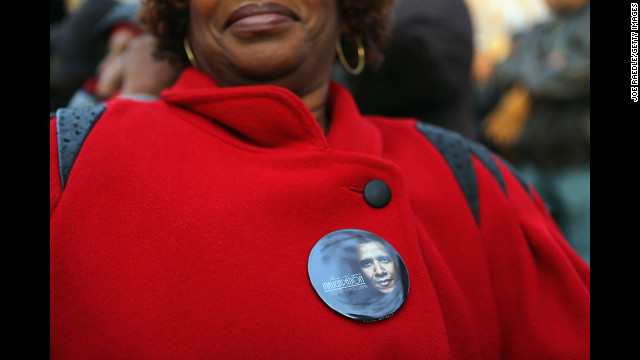 A woman with an Obama button waits near the Capitol on Monday.