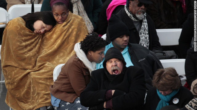 An inaugural attendee yawns while others huddle beneath a blanket Monday at the Capitol.