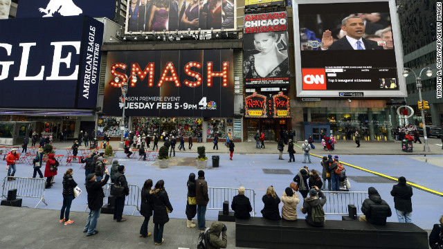 Tourists watch Monday's inauguration from Times Square.