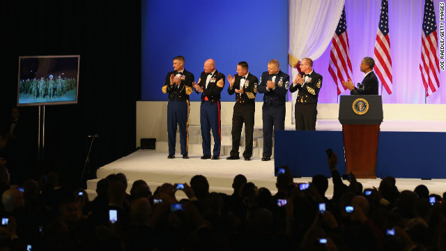 President Obama applauds while speaking with American soldiers in Kandahar, Afghanistan, during Monday's first inaugural ball.