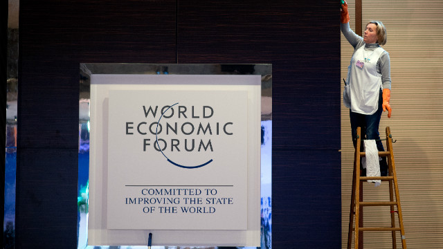 A woman cleans a logo of the World Economy Forum at the congress center on January 21, 2013 at the Swiss resort of Davos.